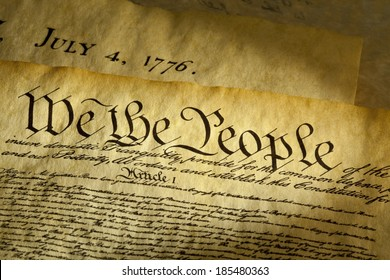 We the People are the opening words of the preamble to the Constitution of the USA. The document underneath is a copy of the Declaration of Independence with the date, July 4, 1776 showing.
