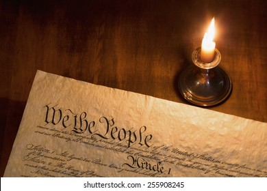We the People are the opening words of the preamble to the Constitution of the United States illuminated by candle light.