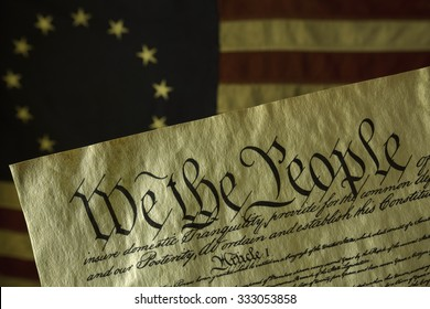 We the People, the opening words of the preamble to the Constitution of the USA, is prominent in this image. The parchment document is in front of on an aged grungy colonial era American flag.