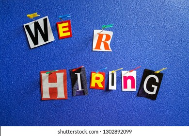 We r hiring letters cut from magazine pinned on blue background