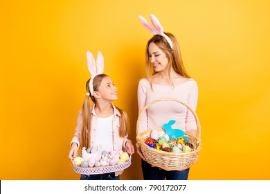 We are ready for the celebration! Cute lovely nice sweet mommy and small daughter holding whisker baskets with colored eggs  cakes and cookies looking at each other isolated on yellow background