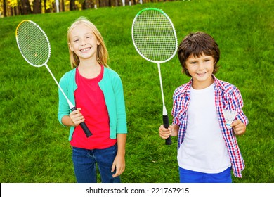 We are ready to play! Two cute little children holding badminton rackets and smiling while standing on green grass together