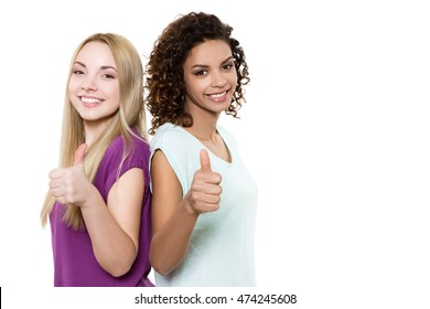 We recommend. Two beautiful happy multicultural female friends posing back to back showing thumbs up copyspace on the side isolated on white