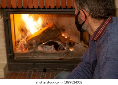 We are sitting at home on self-isolation. A man in a black protective mask looks at the fire in a burning fireplace