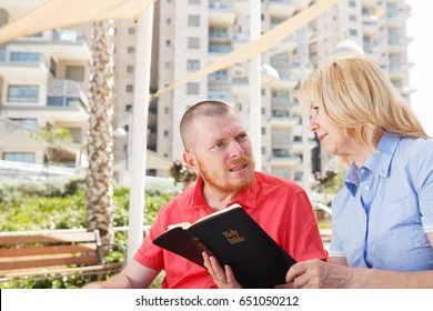 We studying Holy Bible together. Disabled man.