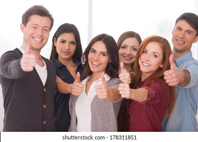 We are successful team! Group of cheerful young people standing close to each other and gesturing