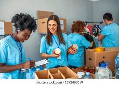 We are successful team of social workers. Group of people working on humanitarian aid project. Teamwork in homeless shelter. Small multi-ethnic group of people working on humanitarian aid project