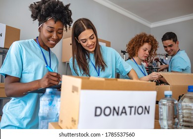 We are team of charitable people. Group of mixed race people working in charitable foundation. People Donating Food To Charity Food Bank Collection In Community Center