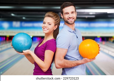 We are a team. Cheerful young man and women looking over shoulders and holding bowling balls while standing against bowling alleys