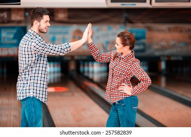 We are a team. Cheerful young man and women looking at each other and giving high five while standing against bowling alleys