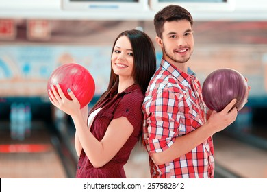 We are a team. Cheerful young man and women posing back to back while standing against bowling alleys and holding balls