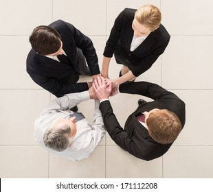 We are team! Top view of four people in formalwear standing close to each other and clasping their hands together