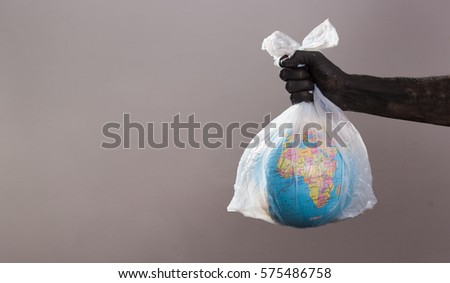 We are trashing planet earth. black hands holding planet earth in plastic bag.