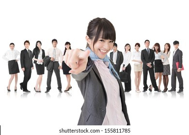 We want you. Asian business woman point at the camera in front of her team. Isolated on the white background.
