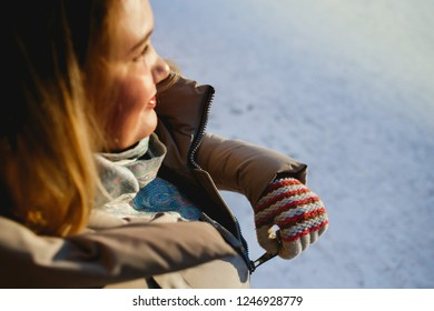 We warm. Woman zips up her jacket on a sunny winter day.