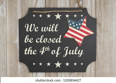 We will be closed he 4th of July text Independence Day on a chalkboard with patriotic USA red and blue star on weathered wood