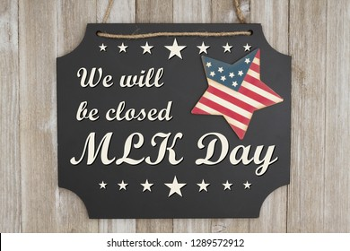 We will be closed MLK Day text on a chalkboard with patriotic USA red and blue star on weathered wood