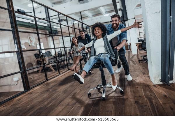 Wir sind die Gewinner!  Vier junge, fröhliche Geschäftsleute in intelligenter, ungezwungener Kleidung, die Spaß beim Rennen auf Bürostühlen und Lächeln haben