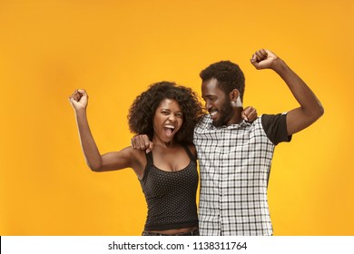We won. Winning success happy afro man and woman celebrating being a winners. Dynamic image of caucasian female and male models on gold studio. Victory, delight concept. Human facial emotions concept.