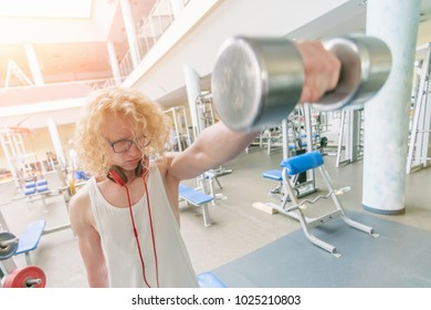Weak curly blonde man holding a dumbbell with a strained face in the sunlight