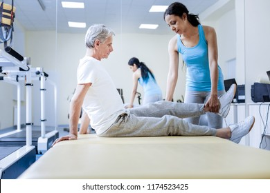 Weak muscles. Qualified experienced medical worker of the modern rehabilitation center warming the weak injured muscles of her tired aged serious patient