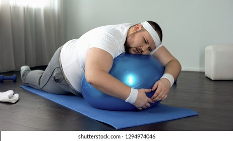 Weak-willed fat man relaxing on fitness ball, home workout break, laziness