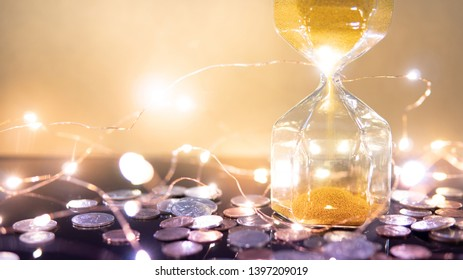 Wealth concept. Global business investment growth. Gold sand running through the modern shape of hourglass with US dollar coins and illuminated decorative Christmas lights on reflective table.