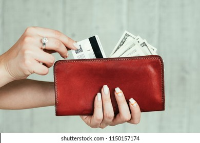 wealth and finances. money earning. cash and credit cards. welfare and income concept. woman hands holding a red leather wallet full of currency.