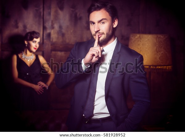Wealth, luxury concepts. Handsome man keep secret and keeping hand in pocket. Beautiful lady stay on background.