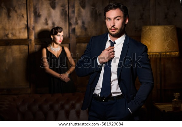 Wealth, luxury concepts. Rich executive man looking away and thinking about vamp woman sitting on background. Beautiful lady ready to marry him.