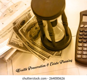 Wealth Preservation & Estate Planning - legal statement. Hourglass, calculator and hundred dollar bills on financial pages of broadsheet newspaper.
