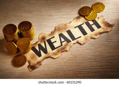 Wealth written on vintage paper and stack of gold coins