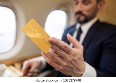 Wealthy businessman sitting in airplane and holding gold card in hand. Focus on card