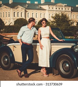 Wealthy couple near classic convertible against royal palace