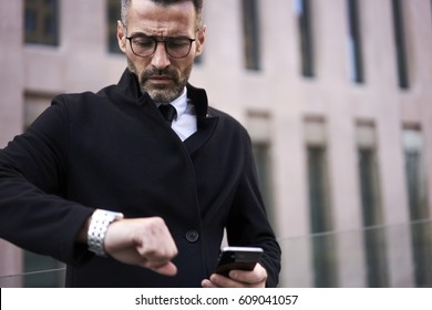 Wealthy entrepreneur in formal wear looking at wrist with watch holding cellular with mobile internet connection and waiting for meeting with colleague, copy space area for your advertise text message