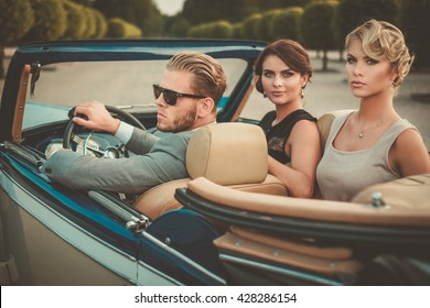 Wealthy friends in a classic convertible