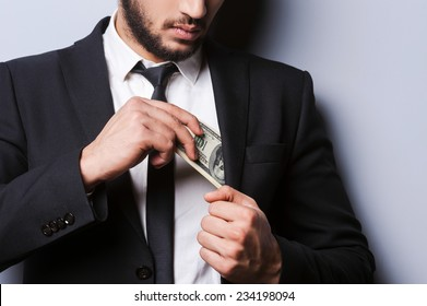 Wealthy handsome. Close-up of young man in formalwear putting money in his pocket while standing against grey background