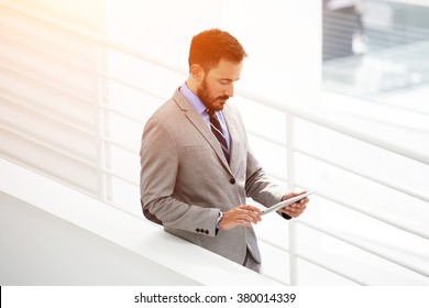 Wealthy male entrepreneur reading news on touch pad about own company during work break in hallway, successful man banker searching information via digital tablet while standing in his office interior