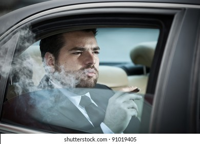 Wealthy man in the back seat of a car smoking