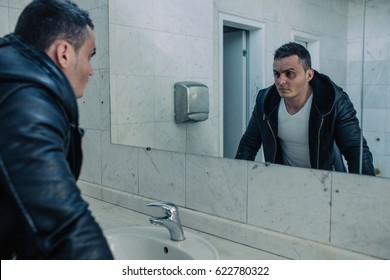 The wealthy man costs in a public toilet. He has a black eye. It seems, he has fought with someone. He has quite severe look.