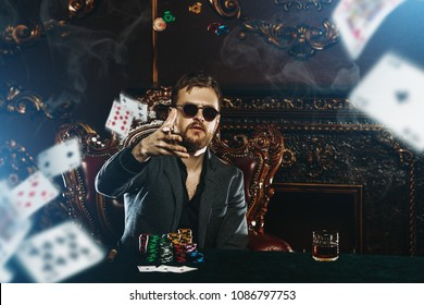 A wealthy mature man playing poker in a casino. Gambling, playing cards and roulette.