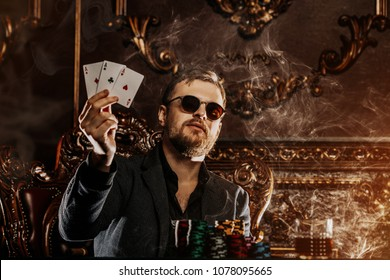 A wealthy mature man smoking cigar and playing poker in a casino. Gambling, playing cards and roulette.