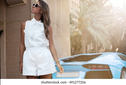 Wealthy woman in elegant clothes standing against car. Luxury life.