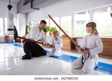 Weapon for aikido. Experienced aikido trainer teaching children to hold Japanese weapon for aikido