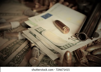 Weapon on dollars with bullets in gunpowder