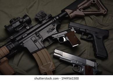 Waffen und militärische Ausrüstung für die Armee, Sturmgewehr (M4A1) und Pistole auf grünem militärischen, einheitlichen Hintergrund.