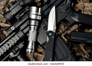Weapons and military equipment for army, Guns tactical flash light and pocket army knife, Assault rifle gun (M4A1) and 9mm pistol on dry leaves forest background.