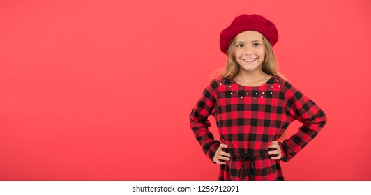 Wear beret like fashion girl. Kid little cute girl with long blonde hair posing in beret hat and checkered dress red background. Beret style inspiration. Fashionable beret accessory for female.