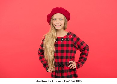 Wear beret like fashion girl. Kid little cute girl with long blonde hair posing in beret hat and checkered dress red background. Fashionable beret accessory for female. Beret style inspiration.