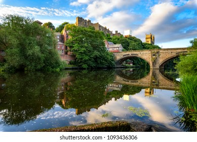 The Wear flows past Durham Castle and Cathedral, beneath Framwellgate Bridge and over a weir.